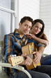 Portrait of young couple with guitar on porch