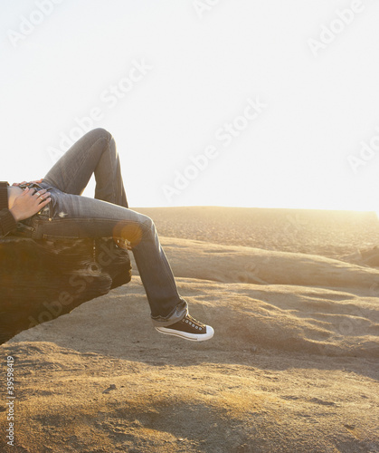 Low angle view of woman laying on log on beach