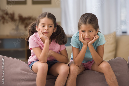 Two girls sitting on couch with hands on chin