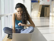 Portrait of young woman with laptop in hallway
