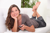 Relaxed woman using a remote control