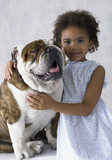 Portrait of young girl hugging bulldog