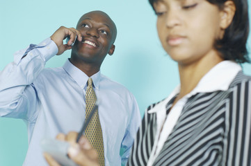 Businessman talking on a cell phone while secretary takes notes