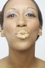 Young woman with sprinkles on her lips