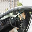 Businesswoman applying makeup inside car