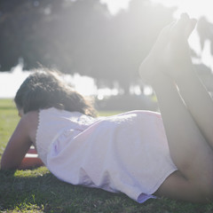 Young girl relaxing on green lawn