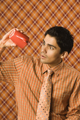 Young man peering into an empty coffee cup