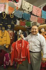 Senior Hispanic man holding a matador outfit