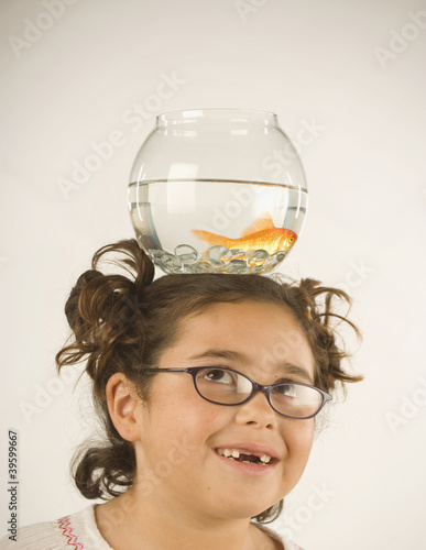 Young girl balancing a fishbowl on her head