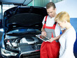 Motor mechanic shows female customer car details on touchpad
