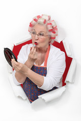 Elderly woman applying lipstick