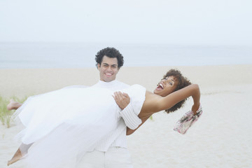 Young man holding his girlfriend on the beach