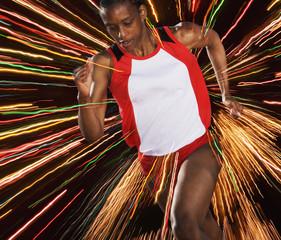 Female athlete running through threads of color