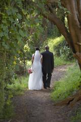 Newlyweds walking along dirt path