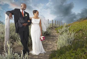 Newlyweds walking on the beach