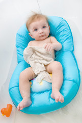 Cute baby girl sitting on a safety seat in the bath