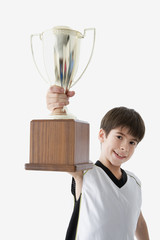 Young athlete holding up trophy triumphantly