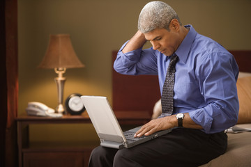 Businessman using a laptop in his hotel room