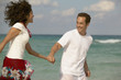 Young couple running hand-in-hand on the beach