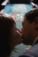 Couple kissing at a gambling table
