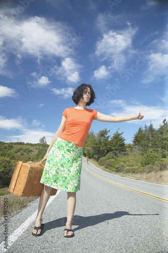 Young woman with a suitcase hitching a ride