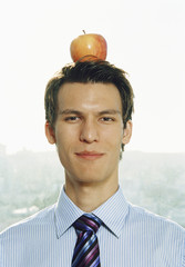 Businessman balancing an apple on his head