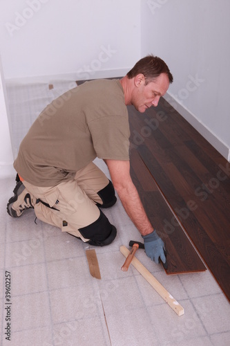 Man at home laying wooden flooring