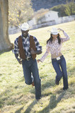 Couple in cowboy outfits walking together