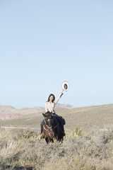 Young woman in a cowboy outfit riding a horse