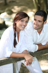 Couple in white leaning on a wooden fence