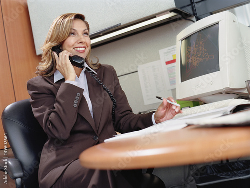 Businesswoman talking on the phone at her desk