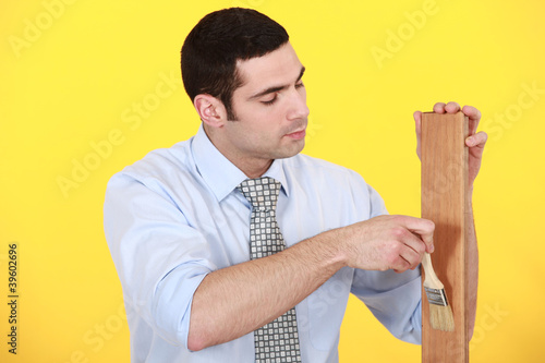 Man applying varnish to a wooden plank