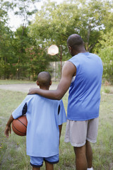 Father and son looking at basketball court