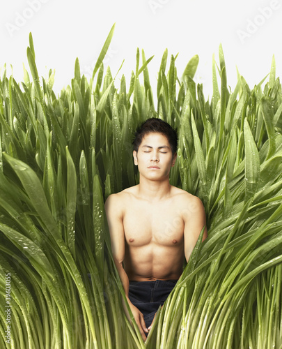 Young man meditating in tall grass