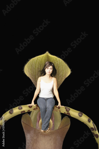 Young woman sitting in a giant plant