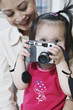Portrait of mother and daughter with camera