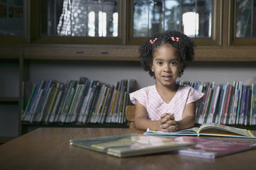 Portrait of girl reading book in library