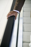 Businessman's hand on rail