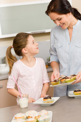 Little girl taste baked cupcakes with mum