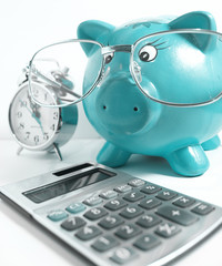 Business concept-piggy bank with glasses,calculator and a clock