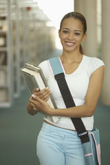 Young woman carrying books and bag