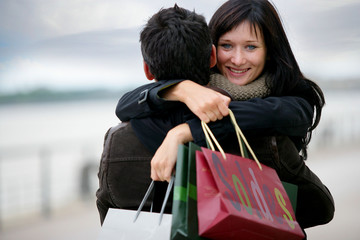Couple with shopping bags hugging