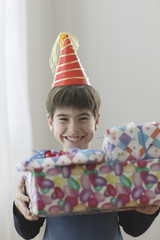 Young boy smiling with birthday presents