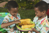 Two young boys sharing grilled corn