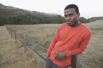 Young man leaning against fence post