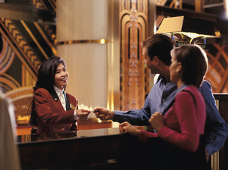 Female receptionist giving room key to couple