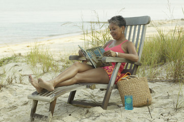 Senior woman reading on beach in lounge chair
