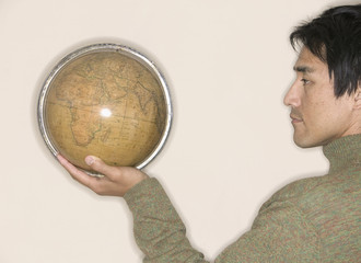 Profile of man holding globe