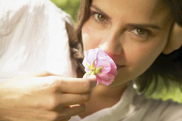 Portrait of woman smelling flower