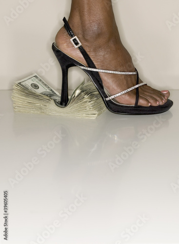Close up of high heel shoe stepping on money